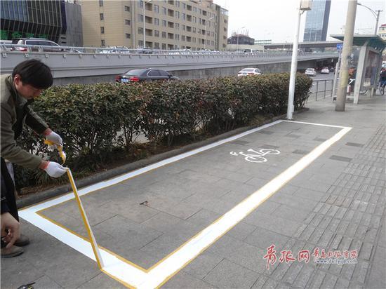 △施工人员在施划共享单车泊位。记者 王凯 摄