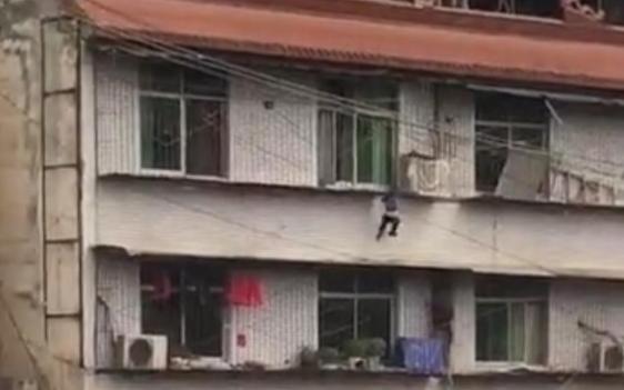 小孩悬吊四楼窗户防护栏 楼下居民拉开棉被当救生垫