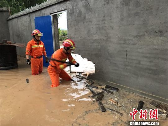 湖北十堰13户居民遭暴雨围困 消防官兵砸墙泄洪