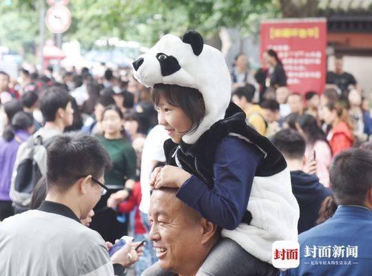 戴着熊猫头饰在成都街头走一走