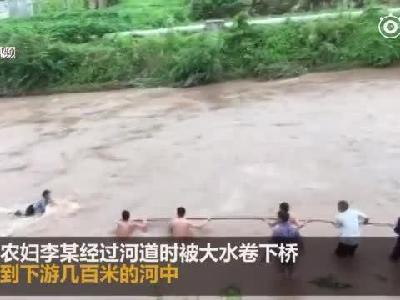 河道突发大水农妇被卷入河中 众人拉竹杆冒险营救