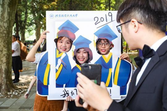 """北京航空航天大学毕业生在""""我们毕业了""""拍照框前拍照。北京航空航天大学 宋超/摄"""