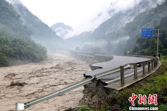 暴雨引发山洪冲毁道路。 桑锦 摄