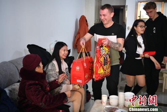 """""""洋女婿""""Liam McCarthy给家中老人拜年并送上新年礼包。 刘忠俊 摄"""