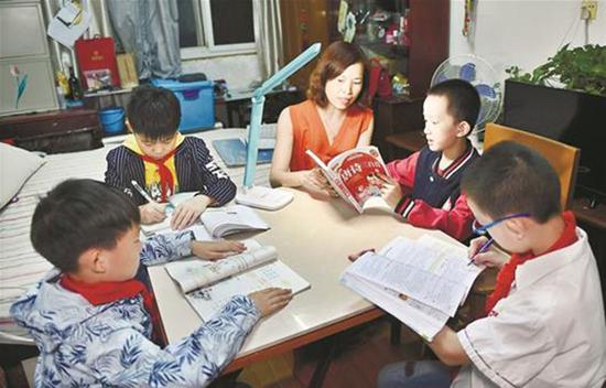 何晓云在家中为学生们辅导功课