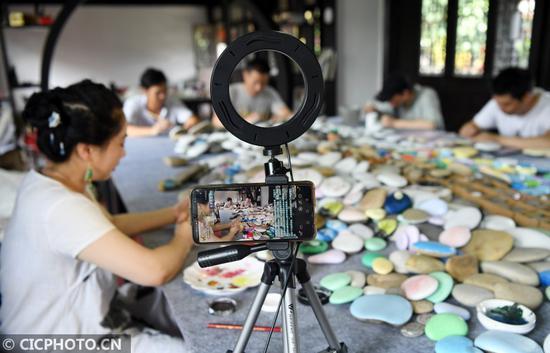 2020年6月12日,在四川省南充市蓬安县嘉陵江石画工坊,画师用网络平台展示嘉陵江石画制作过程。CICPHOTO/刘永红 摄