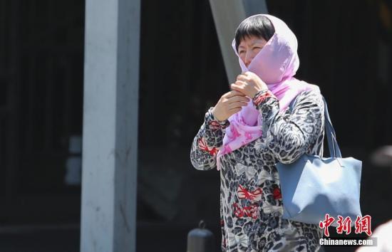 资料图:一女子在高温晴晒天气出行。中新社记者 贾天勇 摄