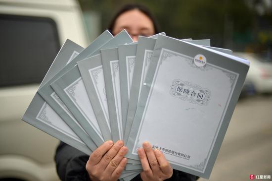 ▲蒋女士展示自己购买的7份保险合同