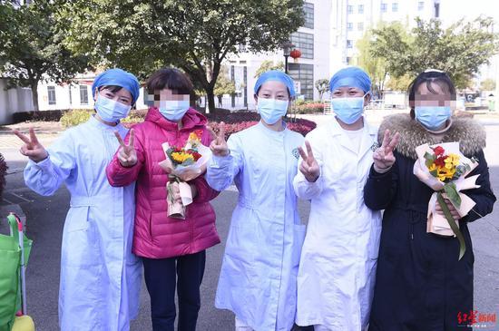 成都市公共卫生临床医疗中心2名出院的患者和医务人员合影