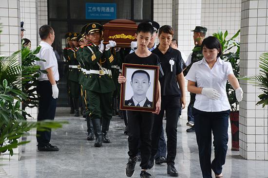 王涛的儿子举着父亲的遗像。澎湃新闻记者胥辉图
