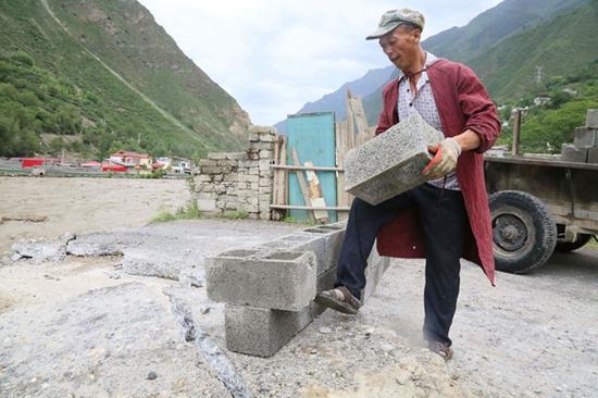 """图为村民秦邦兴正在争分夺秒地搬砖砌着""""隔离墙"""""""