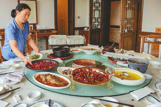 8月14日,成都市锦沙路附近一家酒楼最低消费800元的包间里,服务员正在收拾餐桌,桌上仍剩有不少食物。 本报记者杨树摄