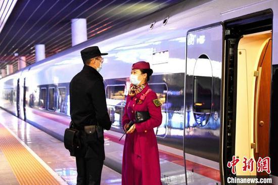 列车长周弋乔与随车机械师交谈。 刘忠俊 摄
