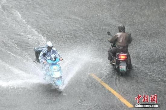 资料图:市民在积水路段骑车出行。王东明 摄