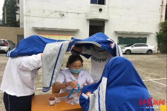 """高考采血遇雨 中学生躬身用衣服为医务人员撑了把""""伞"""""""