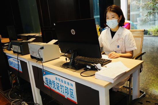 锦江区沙河街道新冠疫苗临时接种点,设有接种凭证打印台,是接种点专门为出国人员等需要凭证的重点人群设立的。魏冯摄。