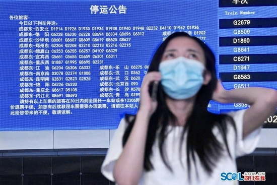 8月17日晚上,在成都火车东站候车厅,一名旅客一边打电话一边观看LED电子显示系统公告的相关停运信息。