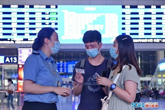 8月17日晚上,在成都火车东站候车厅,工作人员为旅客发放列车停运退票须知卡。