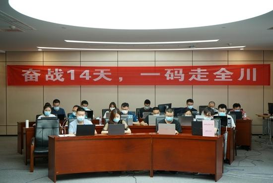 """""""奋战14天,一码走全川。""""8月13日,武侯区天府一街,一条红色横幅挂在四川省大数据中心的大工作间。魏冯 摄"""