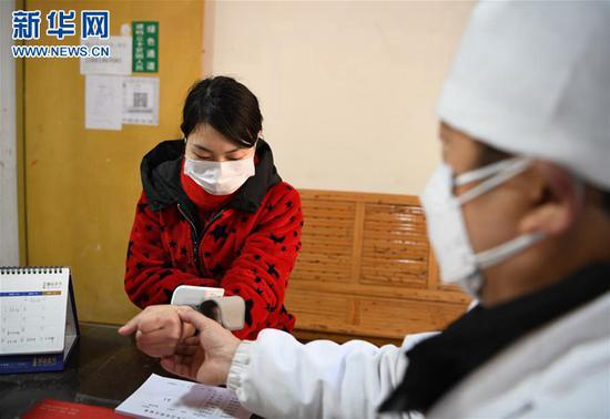 2月19日,在四川省中江县通山乡卫生院,外出务工人员(左)正在检测血压和心率。新华社记者王曦摄