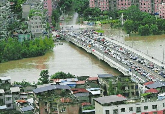 今年8月17日下午,洪峰过境金堂城区,市民在交警指挥下将车辆统一移至工农大桥避险。 喻茂 摄