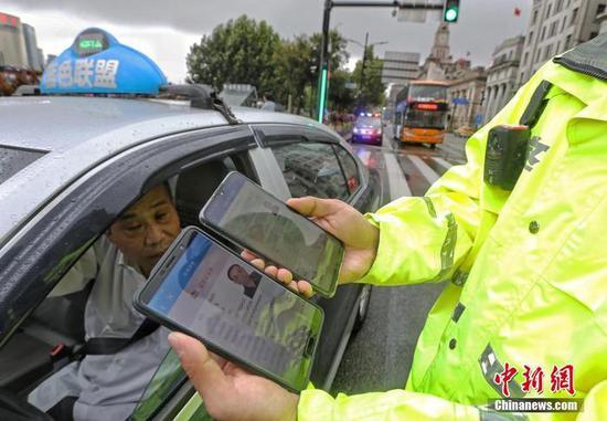 资料图:民警对电子驾驶证进行信息核验。中新社记者 殷立勤 摄
