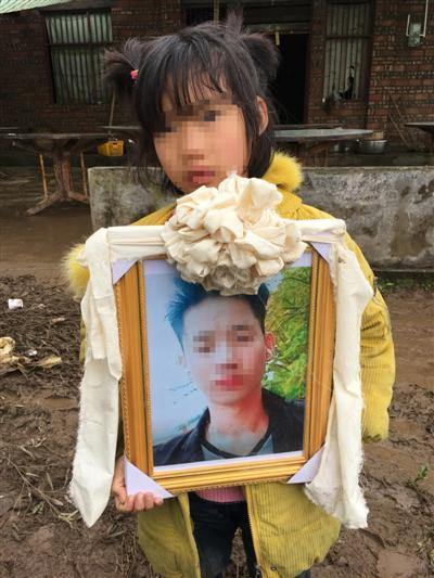 郝中友的女儿抱着他的遗像。