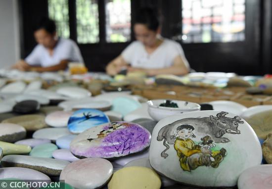 2020年6月12日,四川省南充市蓬安县嘉陵江石画工坊的画师在制作石画。CICPHOTO/刘永红 摄