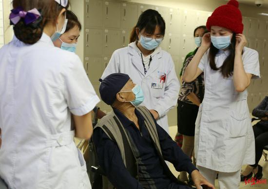 医务人员戴着郭婆婆织的帽子,请王爷爷再次转达谢意 院方供图