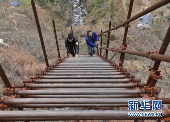 谢杰(右)与同事一起登钢梯上瓦伍村。新华社记者刘坤摄