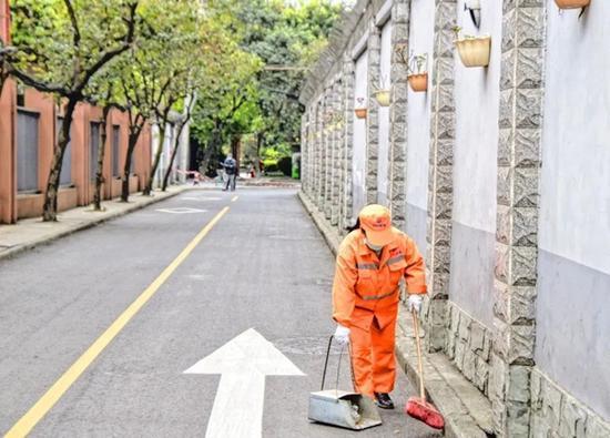 环卫工人仔细打扫校园周边,确保干净整洁。