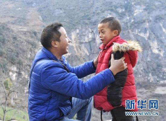 谢杰为瓦伍村一名小朋友穿上送去的外套。新华社记者刘坤摄