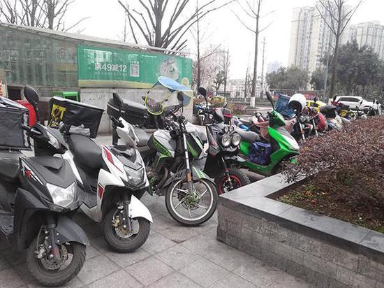 """停放在""""上品拾陆""""小区门口的外卖摩托车。"""