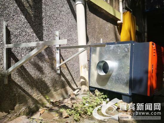 油烟净化器准备安装在居民厨房外墙的楼道上。(宜宾新闻网 曾江 摄)