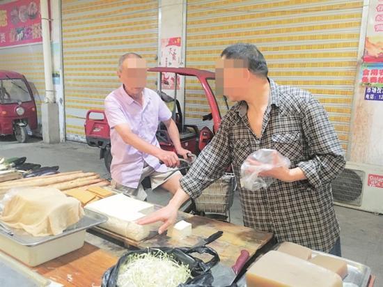 藕园巷农贸市场内未佩戴口罩的商家和市民。