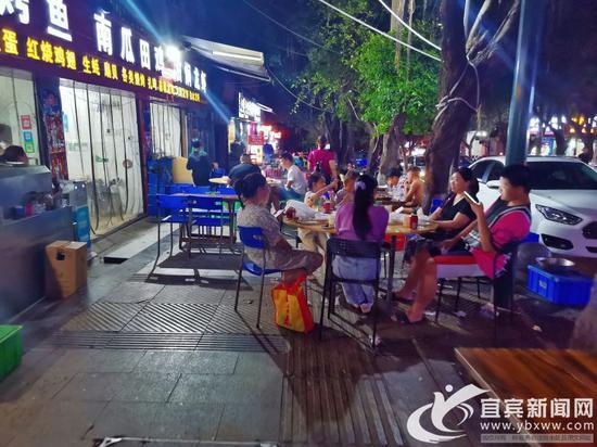 南岸二零二路段的宵夜店,将餐桌摆在了人行道,过往行人无法通行。记者 何东 摄