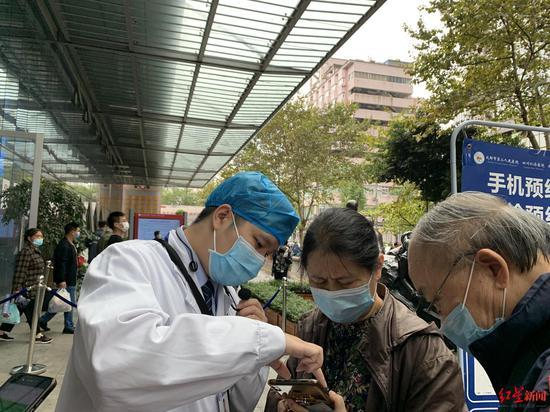 市二医院门前,工作人员指导患者线上预约