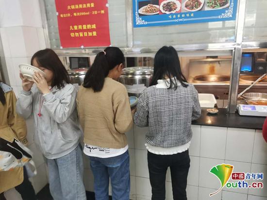 """图为学生正在领取""""大锅汤""""。中国青年网通讯员 廖旭 摄"""