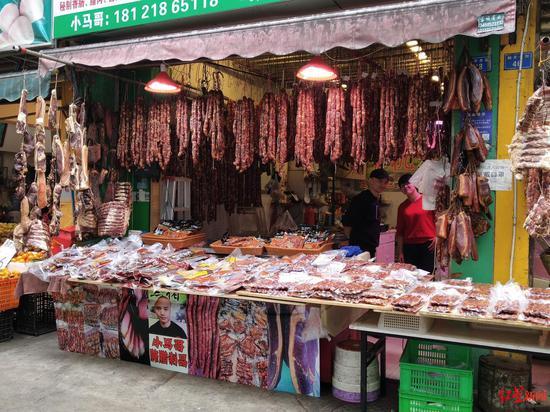 ▲新开寺街的商家门前挂满了香肠腊肉