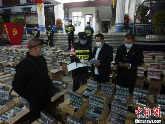 图为民警对该批无合法手续香烟进行清点核验。 邓敦宇 摄