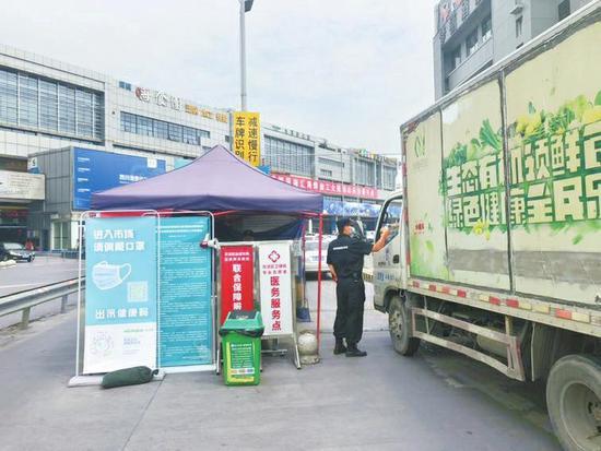 6月30日上午,成都双流区白家农产品批发市场,入口处正在监测来往人员体温。