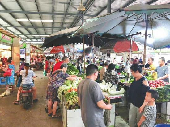 6月30日上午,成都锦江区柳江农贸市场人流密集,但鲜有人戴口罩。 本报记者付真卿摄