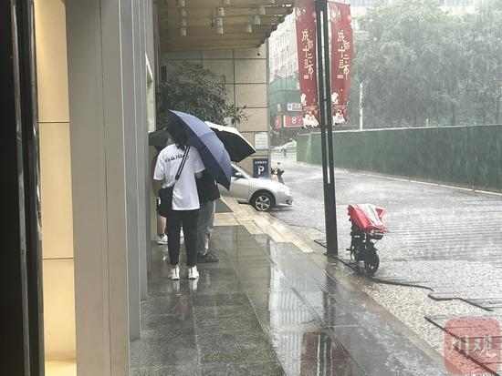 屋檐下避雨的行人