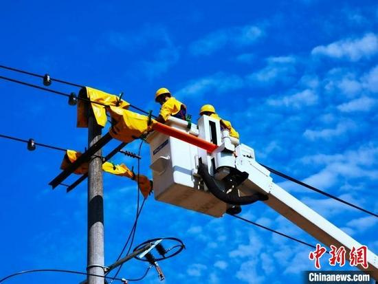 宜宾电力抢修人员带电搭接三相引流线为小区建临时供电。 四川电力供图