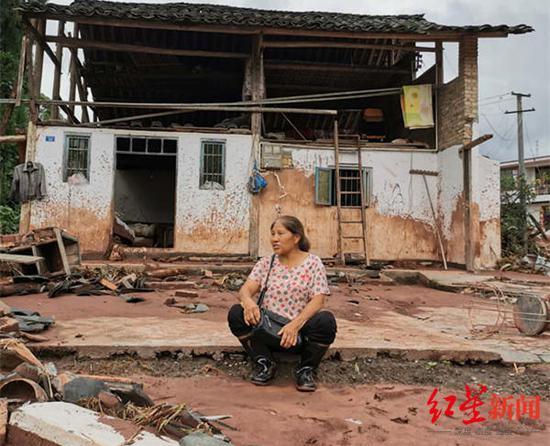 ↑李本兰坐在被洪水冲毁的屋前讲述惊魂一刻
