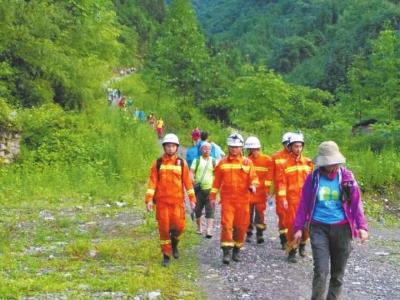 救援人员带领被困者走出险地。