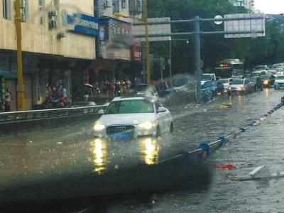 28日,南充顺庆区金鱼岭路积水20多厘米,有车辆被困水中。