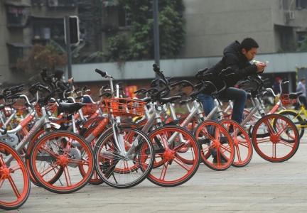 路边停放的共享单车与行人抢道。