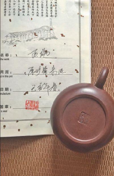 6 月22 日,在宜兴中国陶都陶瓷城买到的刻有国家工艺美术师徐某名字的紫砂壶,商家现场模仿签名售卖。新京报记者 郑新洽 摄
