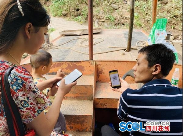 """往返于川黔两地的村民正在微信的方式向船工支付""""过河费"""",5元一人。张其/摄"""